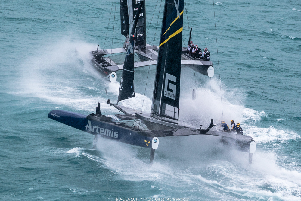 Artemis Racing and Softbank Team Japan just about bear away at the top mark in winds that are hitting the upper limit allowed for racing on day 3 of the playoff semi-finals. Correct hydrofoil choice and precise control seem to be key in the big winds. Photo: ACEA 2017/Gilles Martin-Raget.