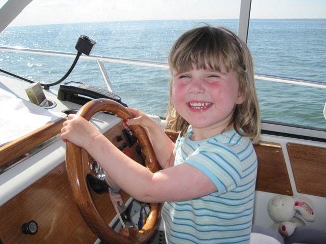 Family boating: child driving motorboat